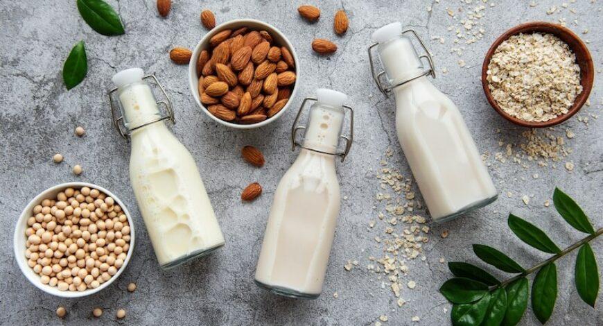 bouteilles avec différents laits végétaux d'avoine, soja et amande